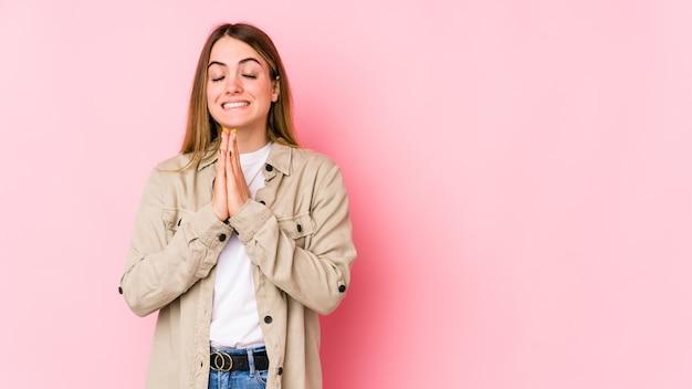 De jonge kaukasische vrouw op roze muur dient hand in bid dichtbij mond