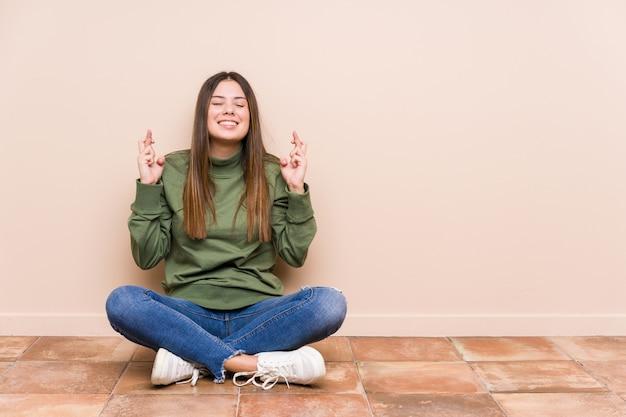 De jonge kaukasische vrouwenzitting op de vloer isoleerde het kruisen van vingers voor het hebben van geluk