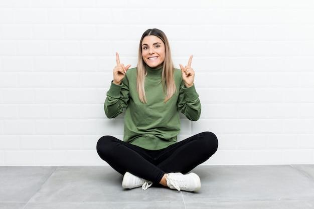 De jonge kaukasische vrouwenzitting op de vloer wijst op met beide voorvingers die omhoog een lege ruimte tonen.