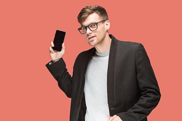 De jonge kaukasische zakenman op rode ruimte die op celtelefoon spreekt