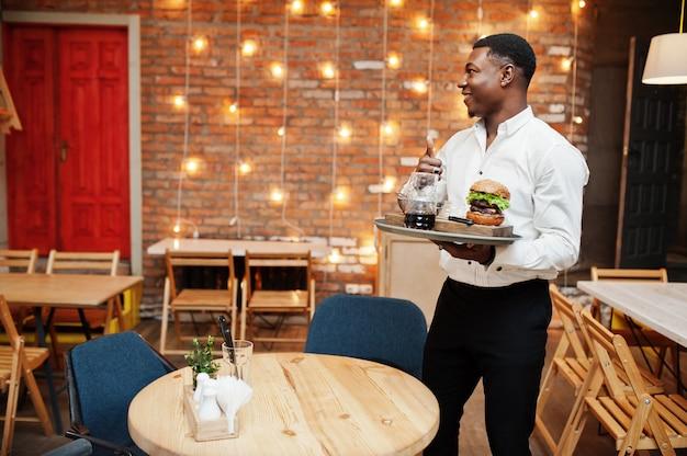 De jonge kelnersmens houdt dienblad met hamburger bij restaurant en toont duim