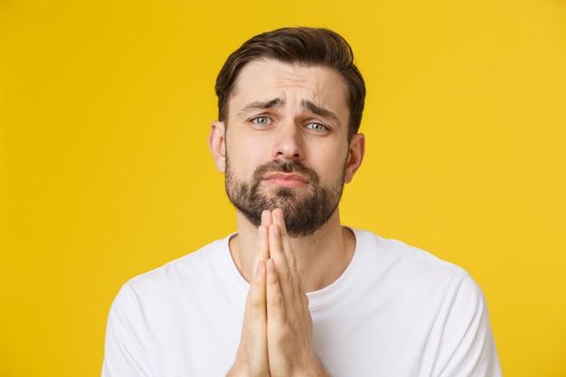 De jonge kerel kleedde terloops geïsoleerd op gele achtergrond, die handen in gebed of meditatie hebben samengebracht, kijkend ontspannen en kalm. Premium Foto