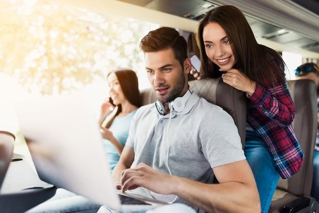 De jonge kerel werkt aan laptop in bus.