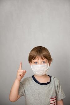 De jonge kindjongen die gezondheidsmasker draagt toont de wijsvinger tegen grijze achtergrond. gezondheidszorginformatie over het coronavirusconcept. nieuw coronavirus