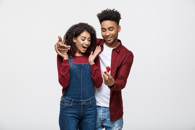 De jonge knappe afrikaanse amerikaanse mens vraagt verrassend haar vriendin voor voorstel