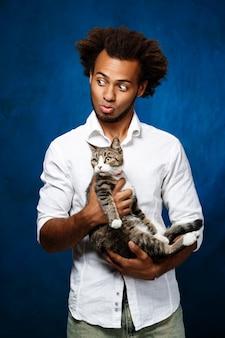De jonge knappe afrikaanse kat van de mensenholding over blauwe muur.