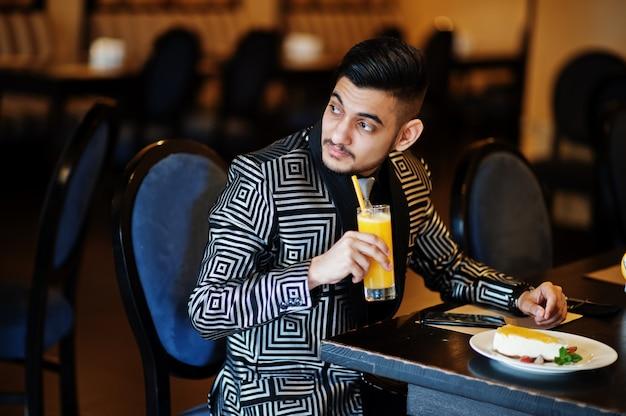 De jonge knappe bedrijfsmens bij avondkostuum drinkt sap op restaurant