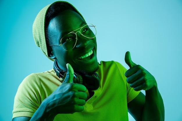 De jonge knappe blij verrast hipster man luisteren muziek met koptelefoon in studio met neonlichten.