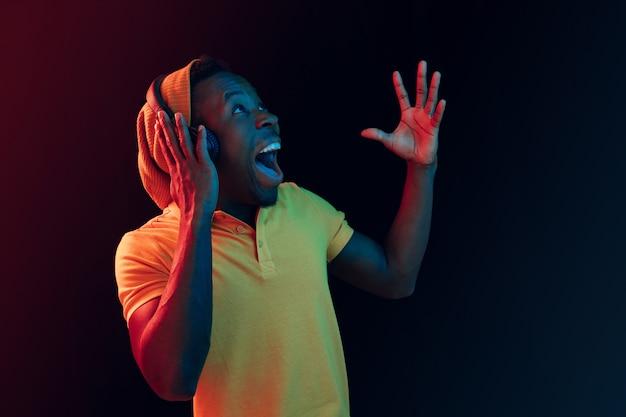 De jonge knappe blij verrast hipster man luisteren muziek met koptelefoon in zwarte studio met neonlichten. disco, nachtclub, hiphopstijl, positieve emoties, gezichtsuitdrukking, dansconcept