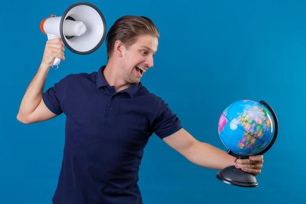 De jonge knappe bol en megafoon die van de mensenholding speels en gelukkig status over blauwe achtergrond kijken