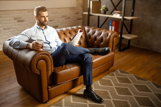 De jonge knappe buisnessmanzitting op bank en drinkt whisky in zijn eigen bureau. hij ziet er recht uit vol vertrouwen. guy houdt dagboek bij. aantrekkelijke kleine glimlach.