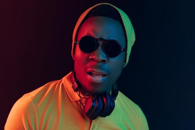 De jonge knappe ernstige triest hipster man luisteren muziek met koptelefoon op zwarte studio met neonlichten.