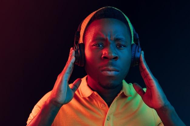 De jonge knappe ernstige trieste hipster man luisteren muziek met koptelefoon op zwart met neonlichten