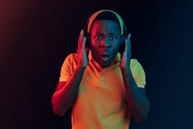 De jonge knappe gelukkig hipster man luisteren muziek met koptelefoon in zwarte studio met neonlichten. disco, nachtclub, hiphopstijl, positieve emoties, gezichtsuitdrukking, dansconcept