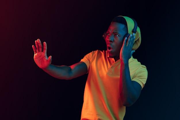De jonge knappe gelukkig hipster man luisteren muziek met koptelefoon op zwart met neonlichten