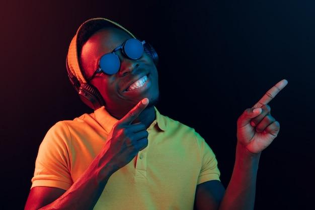 De jonge knappe gelukkig hipster man luisteren muziek met koptelefoon op zwarte studio met neonlichten. disco, nachtclub, hiphopstijl, positieve emoties, gezichtsuitdrukking, dansconcept