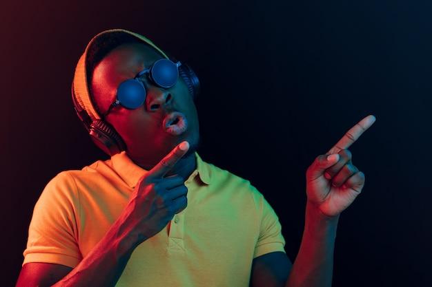 De jonge knappe gelukkig hipster man luisteren muziek met koptelefoon op zwarte studio met neonlichten.