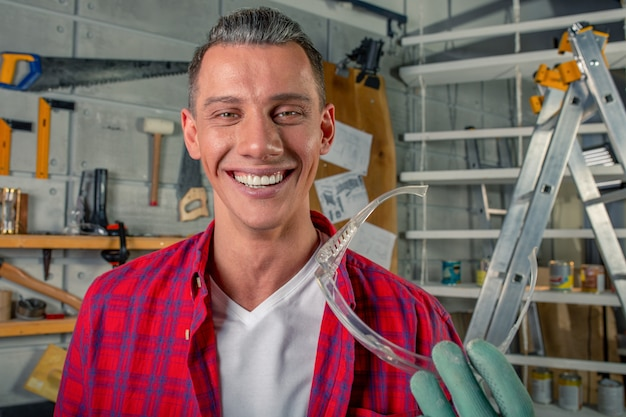 De jonge knappe glimlachende kaukasische timmerman houdt veiligheidsbril in van hem zijn workshop indient