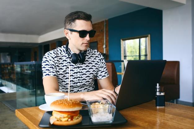 De jonge knappe hipstermens in zonnebril gebruikt laptop in cafetaria. kopje koffie, elektronische sigaret en cheeseburger op houten tafel.