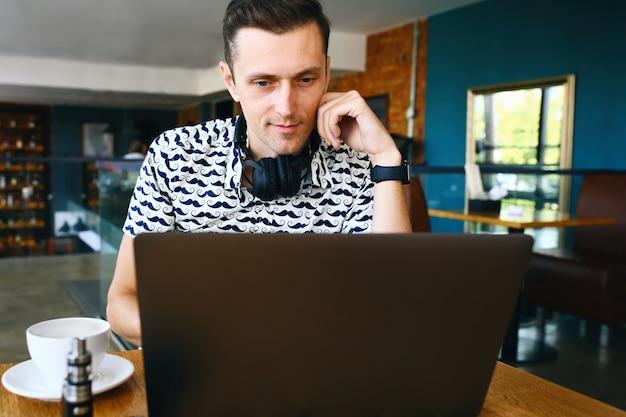 De jonge knappe hipstermens in zonnebril gebruikt laptop in cafetaria.