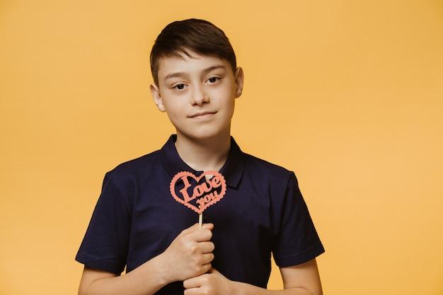 De jonge knappe jongen gekleed in een donkerblauw t-shirt, houdt handgemaakt hart met ik houd van u inschrijving erop. fijne valentijn . mensen oprechte emoties.