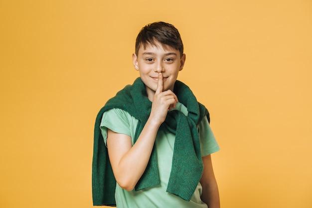 De jonge knappe jongen kleedde zich in toevallig, vragend stil met vinger op lippen te zijn. stilte en geheim concept.