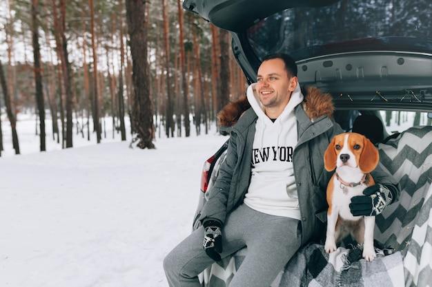 De jonge knappe kerel in een sneeuw de winterbos zit in de boomstam van zijn auto