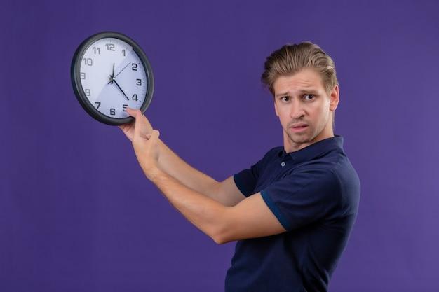 De jonge knappe klok die van de kerelholding camera met verwarren uitdrukking bekijkt die zich over purpere achtergrond bevindt