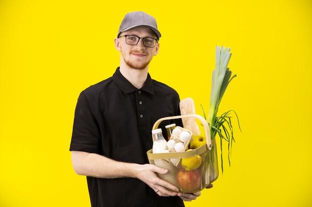 De jonge knappe koerier houdt mand met kruidenierswaren die op gele muur worden geïsoleerd