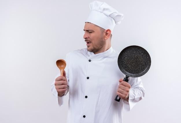 De jonge knappe kok in eenvormige chef-kok doet alsof zingend en lepel en koekenpan op geïsoleerde witte ruimte houdt