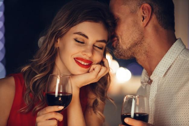 De jonge knappe man fluistert aan zijn vrouw terwijl romantisch diner heeft