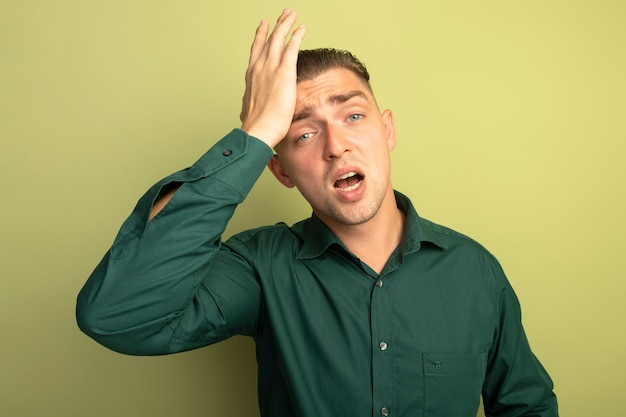 De jonge knappe man in groen overhemd die voorzijde verward met hand op zijn hoofd bekijkt vergat belangrijk ding dat zich over lichte muur bevindt