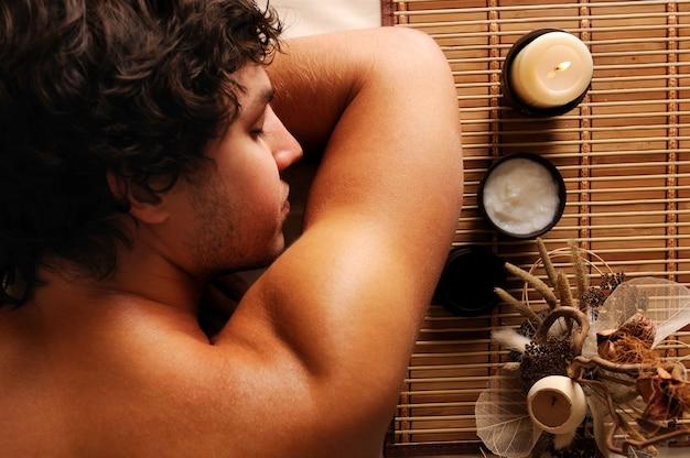 De jonge knappe man ontspanning en recreatie op spa salon. hoge kijkhoek
