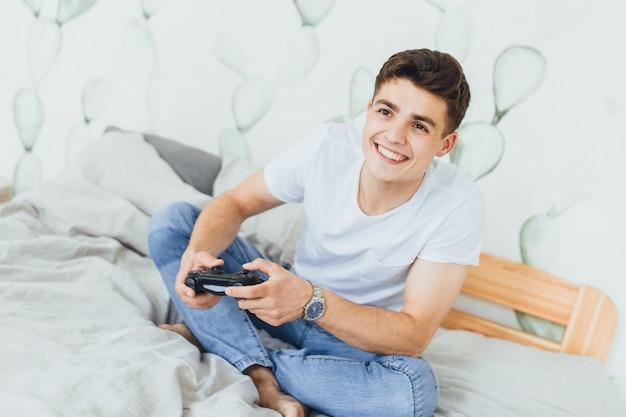 De jonge knappe man op het bed in zijn kamer speelt een spel met een joystick.