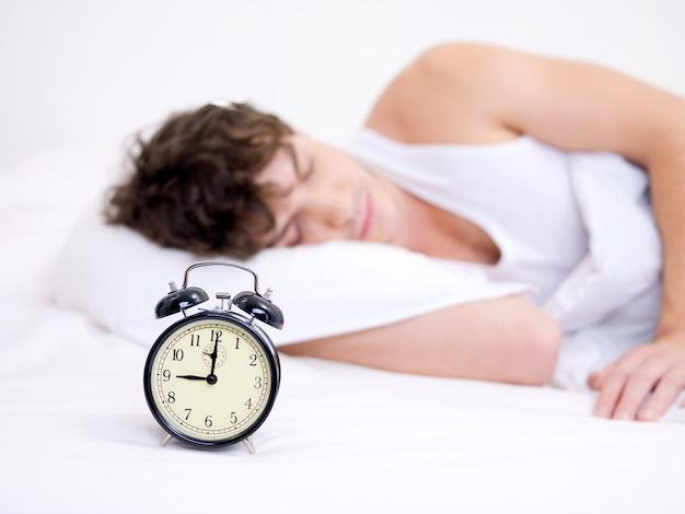 De jonge knappe man slaapt met een wekker in de buurt van zijn hoofd