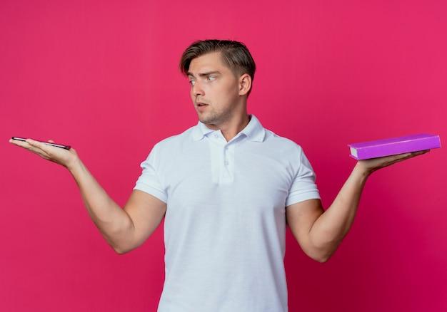 De jonge knappe mannelijke student spreidt handen uit en boek en telefoon op handen die op roze muur worden geïsoleerd