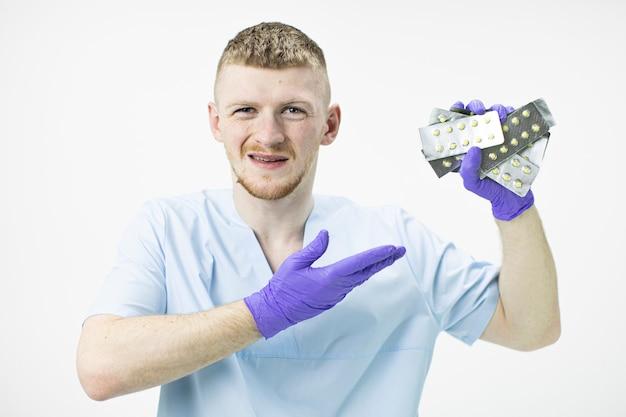 De jonge knappe medische professional houdt veel blisterpillen vast en wijst naar hen met een walgelijke uitdrukking