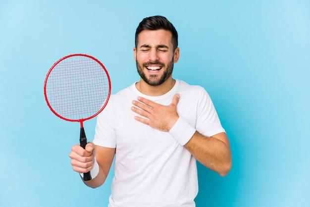 De jonge knappe mens die badminton speelt lacht hardop hand houdend op borst.
