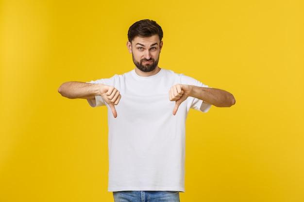 De jonge knappe mens die doend duimen dragen ondertekent neer met handen, meningsverschiluitdrukking.
