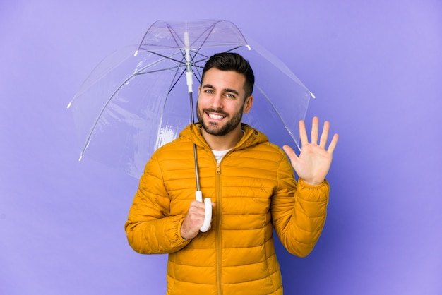 De jonge knappe mens die een paraplu geïsoleerd houden glimlacht vrolijk tonend nummer vijf met vingers.