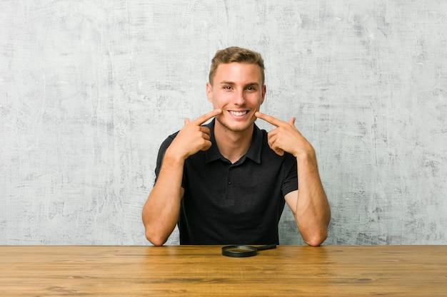 De jonge knappe mens die een vergrootglas houden glimlacht, vingers wijzend op mond.