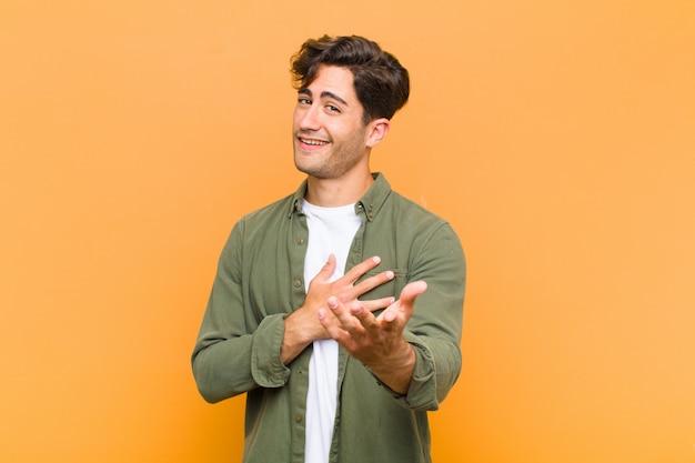 De jonge knappe mens die gelukkig en in liefde voelen, glimlachend met één hand naast hart en andere strekte zich vooraan over oranje muur uit