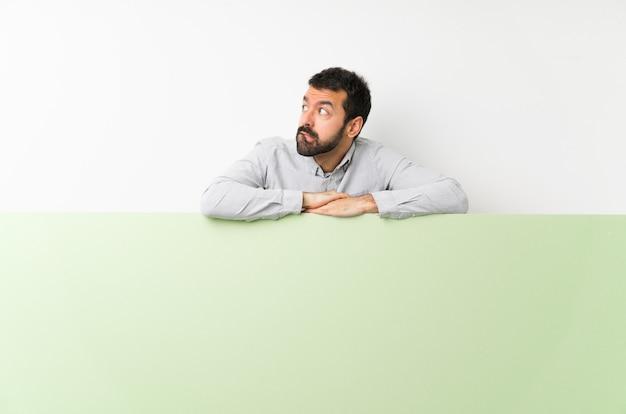 De jonge knappe mens die met baard een groot groen leeg aanplakbiljet met verwart gezichtsuitdrukking houden