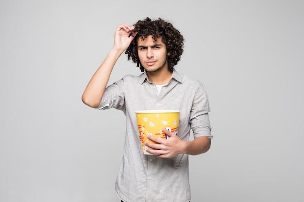 De jonge knappe mens draagt 3d glazen met krullend haar die een kom popcorns over geïsoleerde witte muur houden