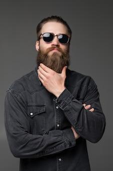 De jonge knappe mens in zonnebril raakt zijn lange die baard op grijze achtergrond wordt geïsoleerd