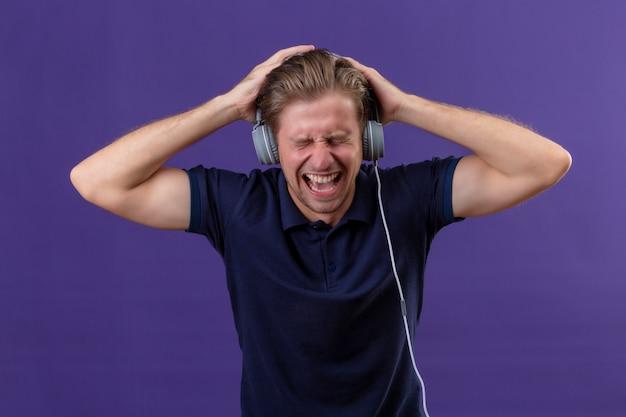 De jonge knappe mens met hoofdtelefoons schreeuwt terwijl muziek met hoog volume luistert dat zich over purpere achtergrond bevindt