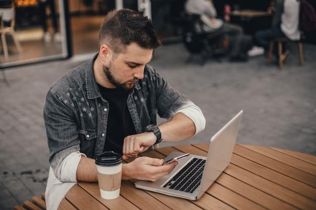 De jonge knappe mens met laptop en kop van koffie zit op stadsstraat