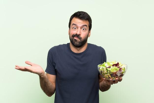 De jonge knappe mens met salade over geïsoleerde groene muur ongelukkig voor begrijpt iets niet