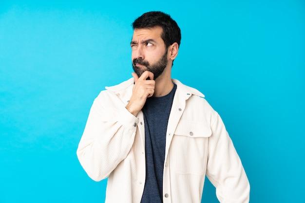 De jonge knappe mens met wit corduroy jasje over geïsoleerde blauwe muur die twijfels hebben en met verwarren gezichtsuitdrukking