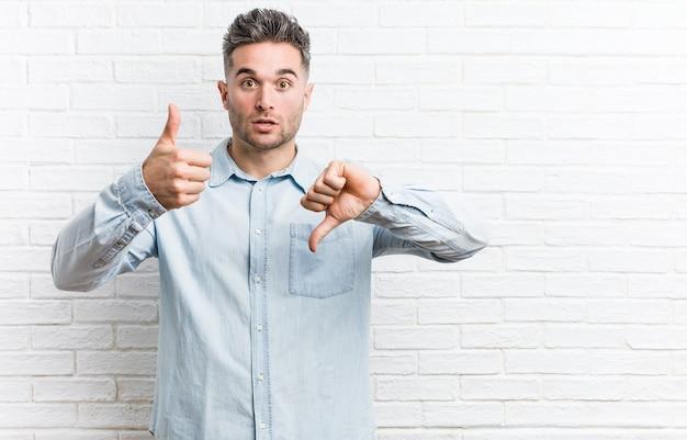 De jonge knappe mens tegen een bakstenen muur die duimen opdagen en duimen neer, moeilijk kiest concept